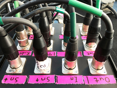 Microphone sound cables connected to the signal box on the stage. Plugged XLR cables.