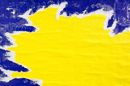 Foto de Yellow and blue torn gloss paper posters with dirty traces of glue on billboard. Can be used for text. - Imagen libre de derechos