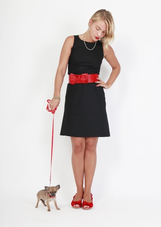 blond woman in black miniskirt with a very small dog on a leash