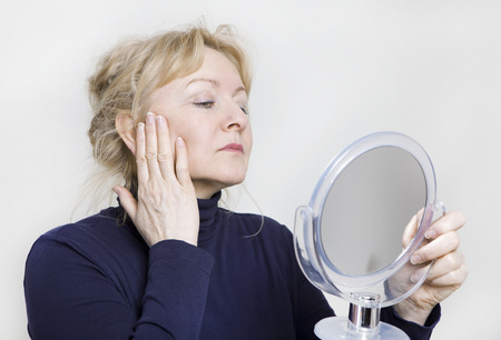 Photo for an older woman looking in a hand mirror on her face - Royalty Free Image