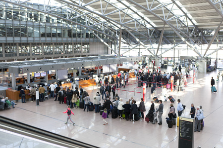Tourists with suitcases at Hamburg airport check in area
