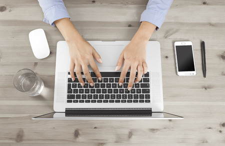 Female fingers typing on a keyboard at a desk, no face