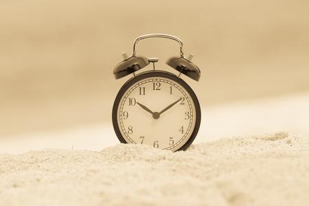 Foto de Vintage alarm clock on sand beach - Imagen libre de derechos