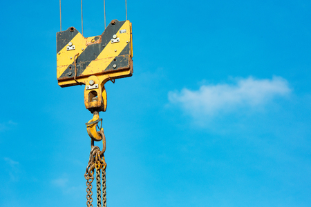 Crane load hook against the sky with trails and chain.