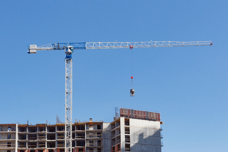 Crane on the background of blue sky and an apartment building under construction.