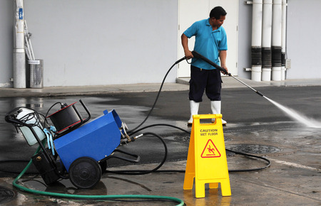 Foto de worker cleaning floor with air high pressure machine - Imagen libre de derechos