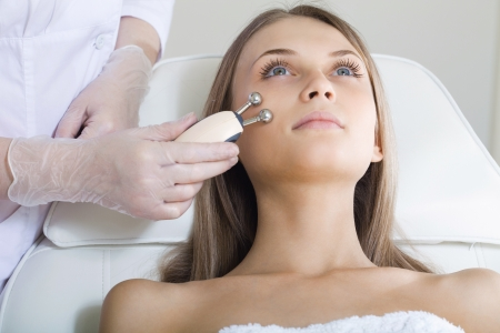 Photo pour woman having a stimulating facial treatment from a therapist - image libre de droit