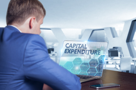 Business, Technology, Internet and network concept. Business man working on the tablet of the future, select on the virtual display: Capital expenditure