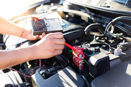 Auto repair technician has inspected the condition of the engine using ammeter, Car repair service concept.