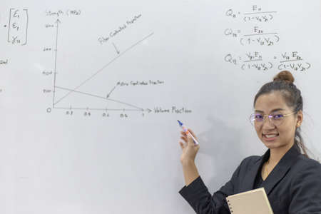 Foto de Teacher is teaching physics to students during the new school days after a long break, High school student classroom, Teacher is writing the instructional formula and explains how to do the exercises. - Imagen libre de derechos