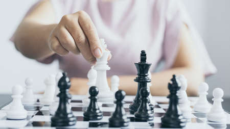 Foto de Businesswoman holding chess to take down opposing players, Proactive business planning and marketing strategy just like playing chess, Business competition and success, Leadership concept. - Imagen libre de derechos