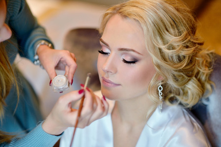 Foto de Wedding makeup artist making a make up for bride. - Imagen libre de derechos