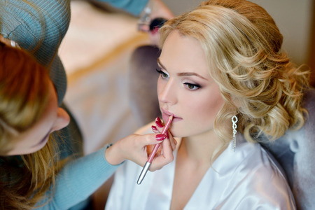 Photo pour Wedding makeup artist making a make up for bride. Beautiful sexy model girl indoors. Beauty woman with curly hair. Female portrait. Bridal morning of a cute lady. Close-up hands near face - image libre de droit