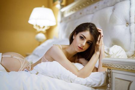 Foto de Beautiful sexy lady in white panties and bra on the bed - Imagen libre de derechos