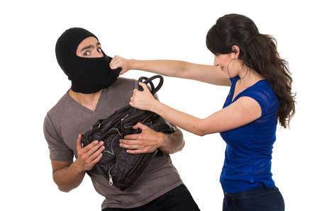 beautiful young girl with hand bag punching masked male thief beautiful young girl with hand bag isolated on white