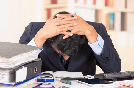 Foto de young stressed overwhelmed business man with piles of folders on his desk holding his head looking down - Imagen libre de derechos