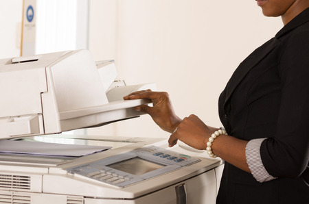 Black office womans hand pressing buttons on a copy machine