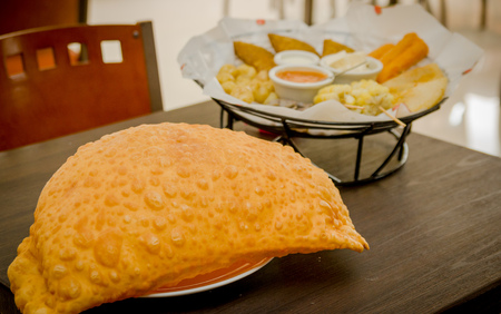 Large empanada on wooden table next to basket of typical latin foods, refreshing restaurant setting.