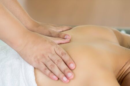 Closeup womans upper back with hands working on giving massage, spa treatment concept.