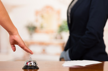 Closeup customer guest hand reaching for traditional reception bell with uniformed employee in background.