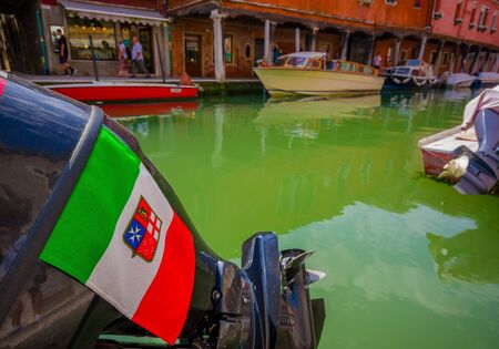 MURANO, ITALY - JUNE 16, 2015: Italy flag and shield on a boat engine above a green water in Murano canals.