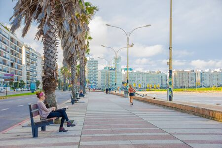 Photo pour MONTEVIDEO, URUGUAY - MAY 04, 2016: people enjoying the afternoon on the board coast with the city as background. - image libre de droit