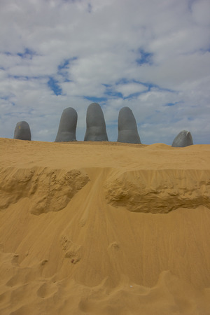 PUNTA DEL ESTE, URUGUAY - MAY 04, 2016: five human fingers emerging from the sand, this sculpture is also known as the hand.