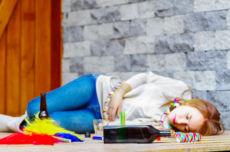 Woman wearing casual clothes lying drunk passed out on wooden surface next to grey brick wall, empty bottle beside her.