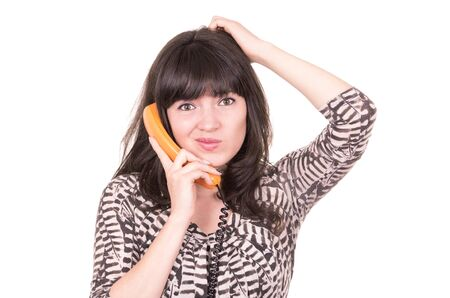 beautiful young confused woman scratching her head using retro orange telephone isolated on white