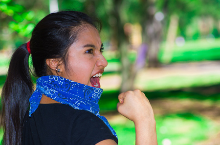 Young brunette woman wearing blue bandana around neck, interacting outdoors for camera, activist protest concept