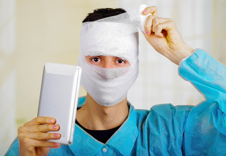 Portrait of a young man with trauma in his head and elastic bandaged around his head holding a tablet