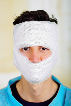 Portrait of a young man with trauma in his head and elastic bandaged around his head