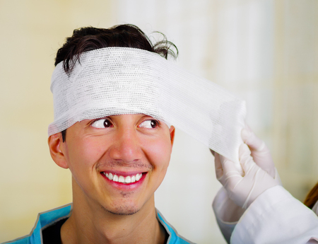 Doctor touching a men s head with trauma in his head and elastic bandaged around his head