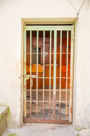 Indoor view with a door with bars, in the old prison Penal Garcia Moreno in the city of Quito