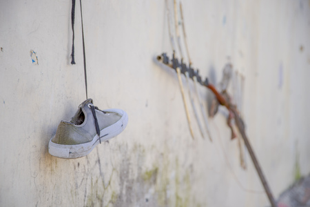 A gray shoes hanging outside of the old prison Penal Garcia Moreno in the city of Quito