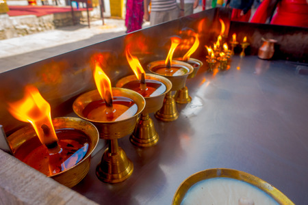 Close up of burning candles inside golden goblets in a temple. Kathmandu, Nepal, Asia