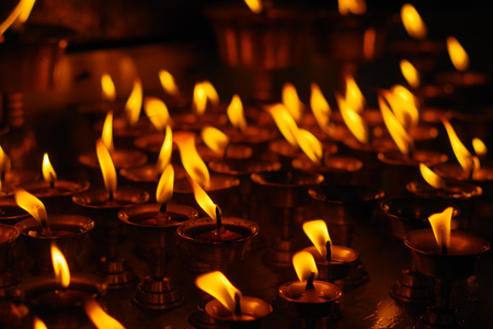 Burning candles in darkness inside temple. Kathmandu, Nepal, Asia.
