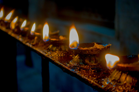 Burning candles in a row, darkness inside temple. Kathmandu, Nepal, Asia