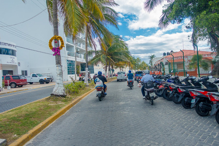 ISLA MUJERES - JANUARY 10, 2018: Outdoor view of some riders with some motorcycles parked in a row in the streets of the city close to Isla Mujeres, Mexico