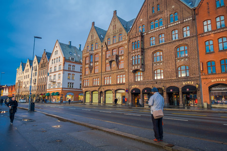 Bergen, Norway - April 03, 2018: People walking close to wooden house, Bryggen, is one of a world heritage site, it contains colorful traditional wooden building lie along the lake