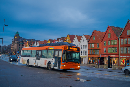 Bergen, Norway - April 03, 2018: Public bus transport close to wooden houses, Bryggen, is one of a world heritage site, it contains colorful traditional wooden building lie along the lake