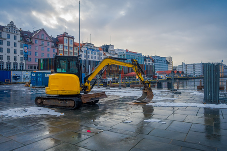 Bergen, Norway - April 03, 2018: Outdoor view of heavy machinary working on renovation walking close to wooden house, Bryggen, is one of a world heritage site, it contains colorful traditional wooden building lie along the lake