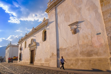 Ciudad de Guatemala, Guatemala, April, 25, 2018: Outdoor view of people in procession spectators walk past colonial buildings backdrop of Agua volcano in UNESCO Wolrd Heritage Site
