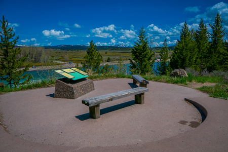Photo pour YELLOWSTONE, MONTANA, USA MAY 24, 2018: Beautiful outdoor view of informative sign and wooden public chair with a view of Jackson Lake Dam in Grand Teton National Park - image libre de droit