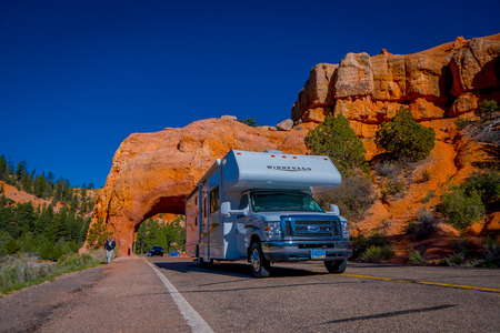 BRYCE CANYON, UTAH, JUNE, 07, 2018: Outdoor view of motorhome trailer crossing throught of red arch natural formation in Monument Valley, Utah