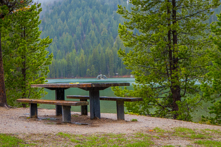 Beautiful outdoor view of metallic and wooden table a chair located in the lakeshore with a gorgeous landscape of Jenny Lake in the Grand Teton National Park, Wyoming in USA.
