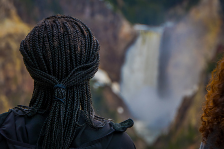 Close up of selective focus of black hair of a woman with a blurred background of the upper Yellowstone Falls in Yellowstone National Park, Wyoming, United States in USA.