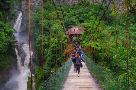 BANOS, ECUADOR, AUGUST, 17, 2018: Unidentified people crossing the bridge close to Bridal veil Manto de la novia waterfall in Cascades route, Banos, Ecuador