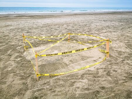 Photo pour Protected Sea Turtle Nest. Barricaded sea turtle nest with yellow tape and ground meshing on the beach. - image libre de droit