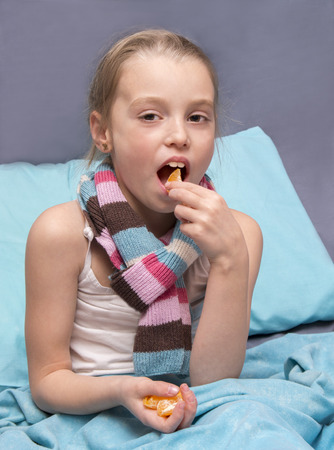 school-age child is recovering from an illness and eating vitamins